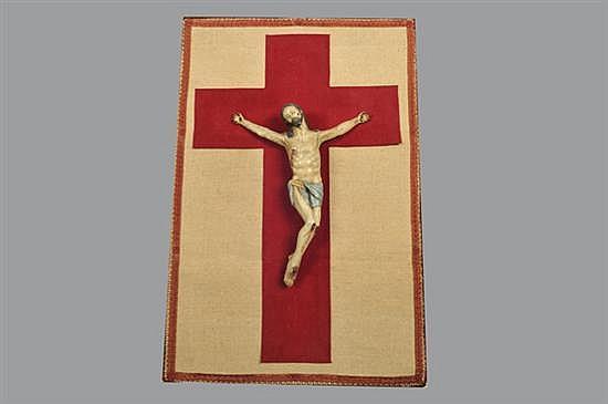 Cristo. En madera tallada, policromada. Montado sobre manto de tela rectangular con detalle central cruciforme. Incluye tachuelas.