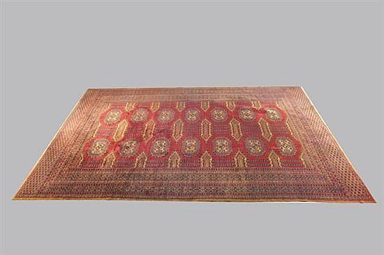 Alfombra pakistaní. Estilo Boukhara. Elaborada en lana, color rojo. Diseño con flequillos y motivos geométricos en cenefa y cartela.