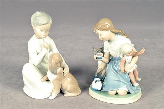 Lote de porcelana. Origen español. Lladró, acabado brillante. Consta de: a) Niño con perro. b) Niña con muñeca y gato. Piezas: 2