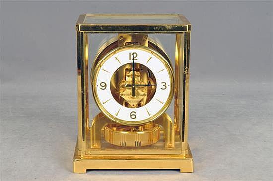 Reloj Atmos. Maquinaria suiza. Marca Jaeger LeCoultre. En metal dorado. Diseño con esfera blanca, índices arábigos y triangulares.