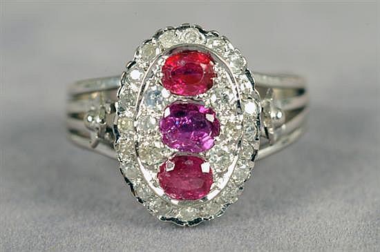 Anillo para dama. Medida 8 1/2. En paladio. Diseño con tres rubíes en corte redondo y brillantes corte 8x8. Peso: 4.9 grs.