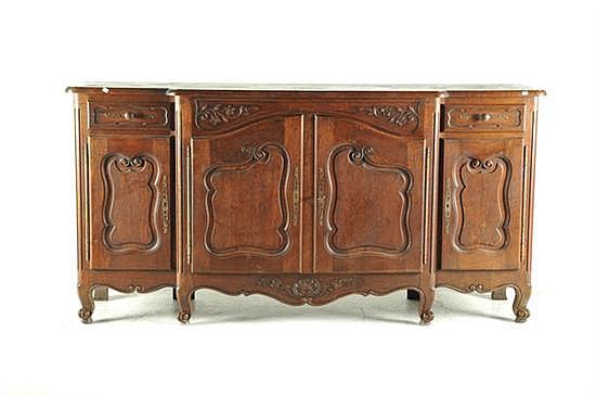 Trinchador estilo Luis XV. Elaborado en madera tallada. Decoración vegetal y mixtilínea. Con 4 puertas y 2 cajones. Presenta raspones.