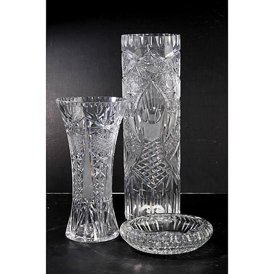 Tres piezas de cristal. Diseño facetado y cortado. Decoración con motivos geométricos. Consta de: 2 floreros y cenicero. Detalles de co