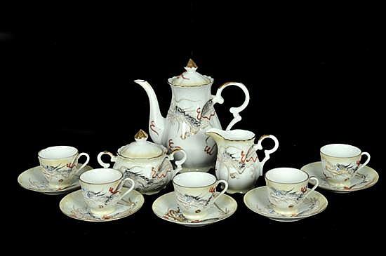 Juego de té. Elaborado en porcelana japonesa. Decoración de dragones en relieve y detalles en esmalte dorado. Consta de 13 piezas.