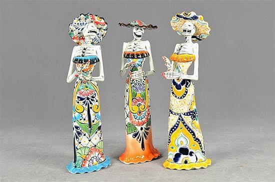 Catrinas. Origen mexicano. En cerámica policromada, acabado brillante. Decoradas con motivos florales. Presentan piezas móviles. 3 pz.