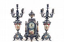 Guarnición. Origen italiano. En metal y porcelana. Consta de: a) Reloj de mesa. b) Par de candelabros. Piezas: 3