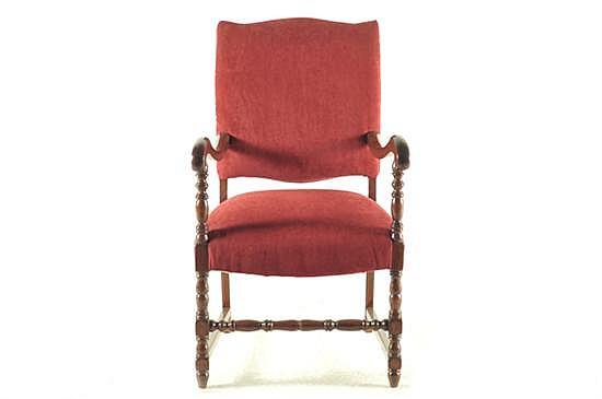 Sillón. En madera tallada. Diseño con soportes y chambrana torneada, asiento y respaldo acojinado con tapicería en color rojo.