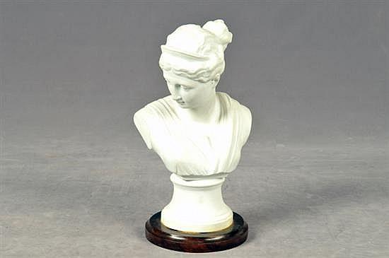 Busto femenino. Elaborado en porcelana biscuit. Diseño con base circular de madera. Dimensiones: 25 cm.