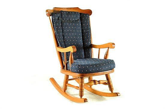 Mecedora. Estilo americano. En madera tallada. Diseño con respaldo calado, cojines con tapicería azul desmontable y chambrana de caja.