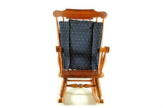Mecedora. Estilo americano. En madera tallada. Diseño con respaldo calado, cojín con tapicería azul desmontable y chambrana de caja.