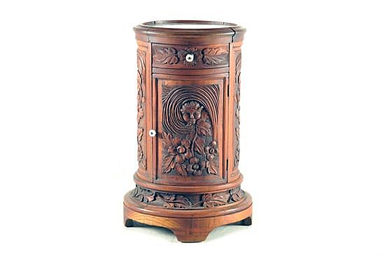 Mesa-Pedestal. En madera tallada. Diseño oval. Con un cajón, una puerta abatible (moureau) y cubierta de vidrio. Decorado floral.