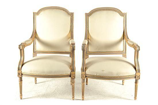 Par de sillones. Estilo neoclásico. En madera dorada. Diseño con asiento y respaldo acojinado en color beige; patas tipo columna. 2 pz.