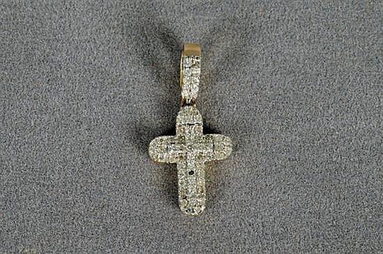 Dije. Elaborado en oro de 14k. Diseño a manera de cruz con bordes redondeados; con brillantes en corte completo, peso exacto 0.20 Ct.