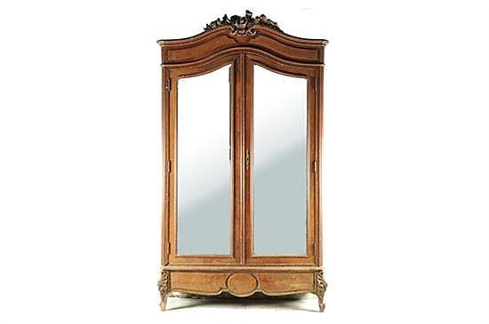 Ropero. Estilo francés. Elaborado en madera tallada. Diseño con 2 puertas y dos espejos biselados, 3 entrepaños, un cajón y remate.