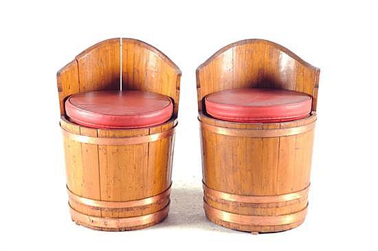 Par de sillones. En madera tallada. Diseño tipo barril, con cojines desmontables y aplicaciones de metal. Total de piezas: 2