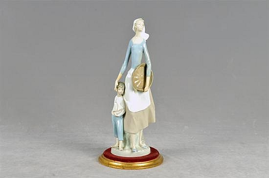 Mujer con niña. Elaborada en porcelana Lladró, acabado brillante. Diseño con base de madera añadida. Presenta ligeras rupturas.