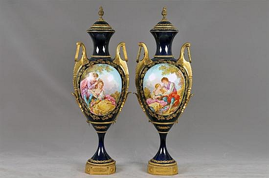 Par de tibores. Origen francés. Elaborados en porcelana Sévres, acabado brillante. Diseño esmaltado, con dos asas y bases metálicas.