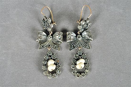 Par de aretes largos. En oro de 10k. Diseño a manera de rosetas con colgantes en forma de moños con perlas blancas. Peso: 17.9 grs.