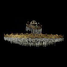 Candil. Siglo XX. Elaborado en metal dorado. Diseño oval. Para 20 luces. Decorado con hilos y motivos vegetales.