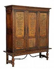 A SPANISH PROVINCIAL STYLE OAK AND LEATHER INSET CABINET