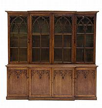 A GOTHIC REVIVAL CARVED OAK BREAKFRONT BOOKCASE