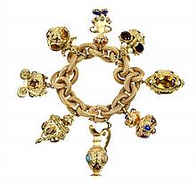 A LARGE 18 KARAT YELLOW GOLD CHARM BRACELET WITH GEMSTONES