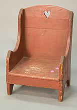 Primitive child's chair with heart carved back on bootjack ends in old red paint (repair to back).Rht. 19 1/2 in.; wd. 13 in.