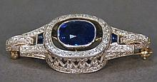 Anton Horvat platinum, sapphire and diamond brooch having center set with a cushion cut blue sapphire measuring 10 x 9.5 x 5.55mm, a...