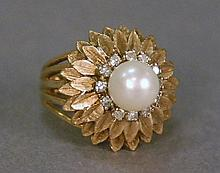 14K gold ring set with center pearl surrounded by twelve small diamonds. 9.9 grams; size 6 1/2