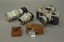 Vintage Leica M2 camera with three lenses, flash and Leica meter along with a tripod.
