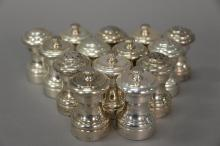 Seven pairs of sterling silver salt shakers with pepper mills.