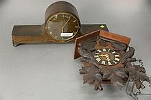 Two clocks including a mantle clock by Gebruder Junghans and a cuckoo clock. mantle: ht. 9 in.; lg. 22 in., cuckoo: ht. 15 in.; wd....