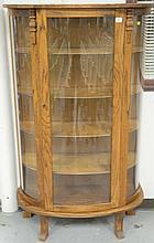 Oak bowed glass cabinet.