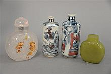 Four Oriental snuff bottles including one green hardstone, one clear quartz carved with russet fish, and two porcelain blue , white ...