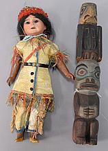Two piece lot to include an Indian totem, early 20th century, ht. 10 1/2 in. and Indian bisque head doll in hyde clothes, ht. 10 in.