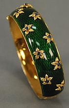18K gold and green enameled bangle style bracelet mounted with gold flowers set with blue stones. 47 grams