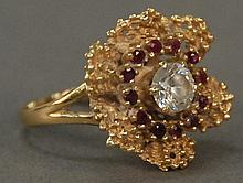 14K gold ring, floral design set with center diamond approximately .80 cts. surrounded by red stones. 9.7 grams