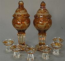 Bohemian glass eight piece lot including two covered jars and six short glasses, amber to clear. covered jars: ht. 11 1/2in.