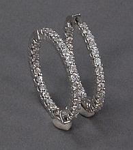 Pair of 18k white gold hoop eternity earrings, each set with twenty seven diamonds.