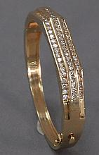 14K gold bangle bracelet set with three rows of twenty one diamonds, sixty three diamonds total, 49 grams.