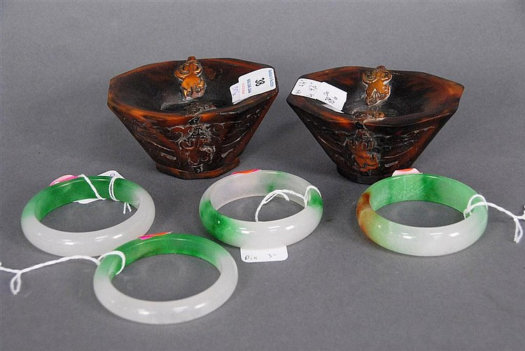Group of six Oriental items; pair of carved horn cups hts. 2 1/4in.; lg. 4 1/2in. and four jadeite bracelets dia. 3in.