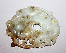 A CHINESE PIERCED JADE-LIKE CARVING OF TWO CONFRONTING DRAGONS