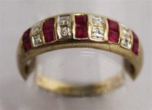 A 9CT YELLOW GOLD RUBY AND DIAMOND HALF HOOP RING.