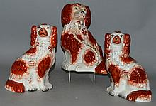 THREE STAFFORDSHIRE BROWN AND WHITE SEATED KING CHARLES SPAN