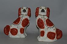 A PAIR OF STAFFORDSHIRE BROWN AND WHITE SEATED KING CHARLES