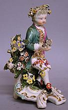 A LATE 18TH CENTURY DERBY FIGURE OF A BOY, seated with flowe