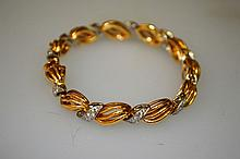 A LADIES 18K YELLOW GOLD AND DIAMOND BRACELET, as a swirl in