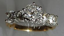 AN EMERALD CUT DIAMOND RING, with baguette diamond shoulders