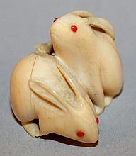A SMALL JAPANESE IVORY CARVING OF A PAIR OF RABBITS