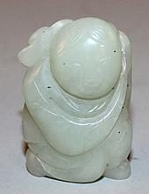 A LATE 19TH/EARLY 20TH CENTURY CHINESE CELADON JADE CARVING OF A KNEELING BOY